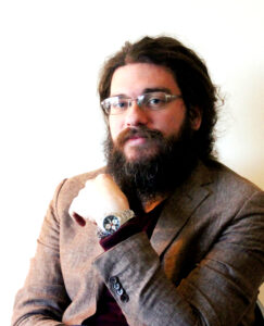 A bearded man with glasses and long hair wearing a brown jacket